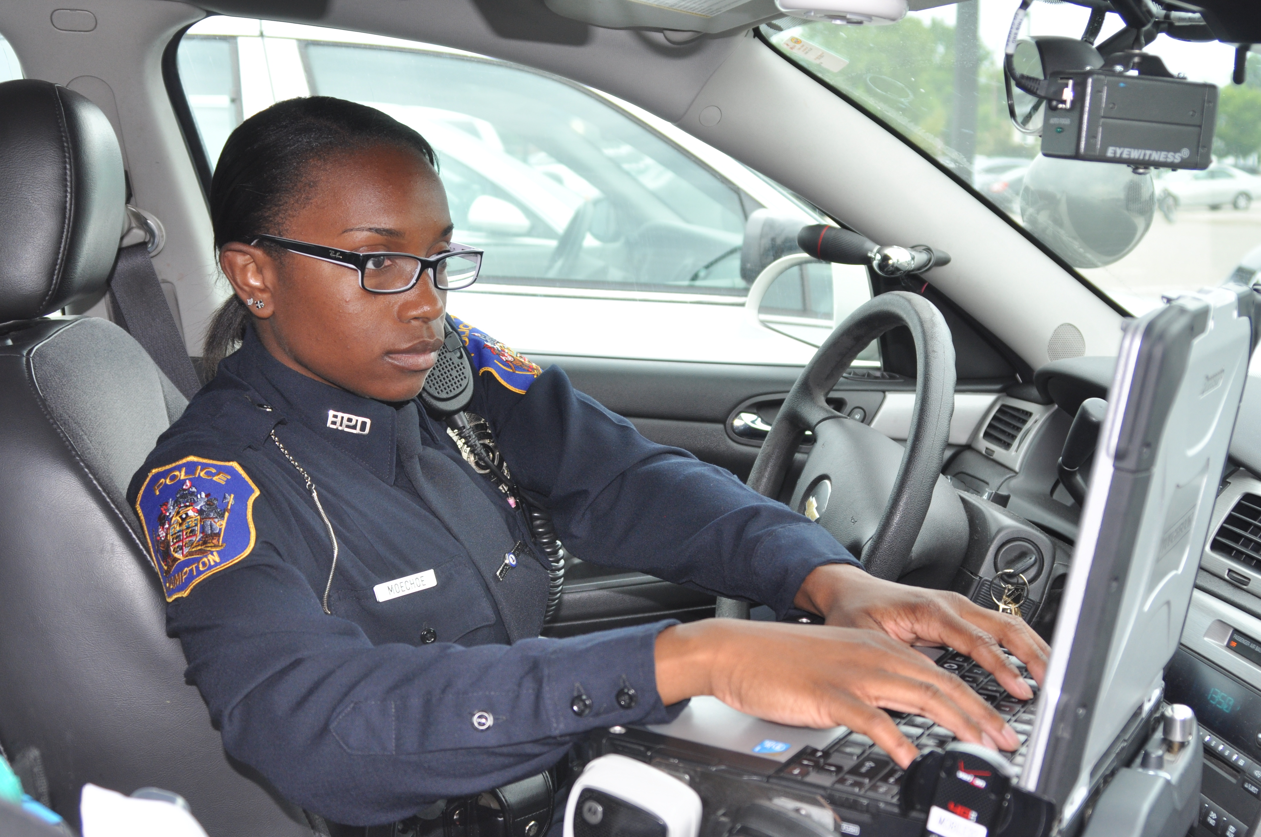 Female Police Officer in Police Vehicle Typing on Computer