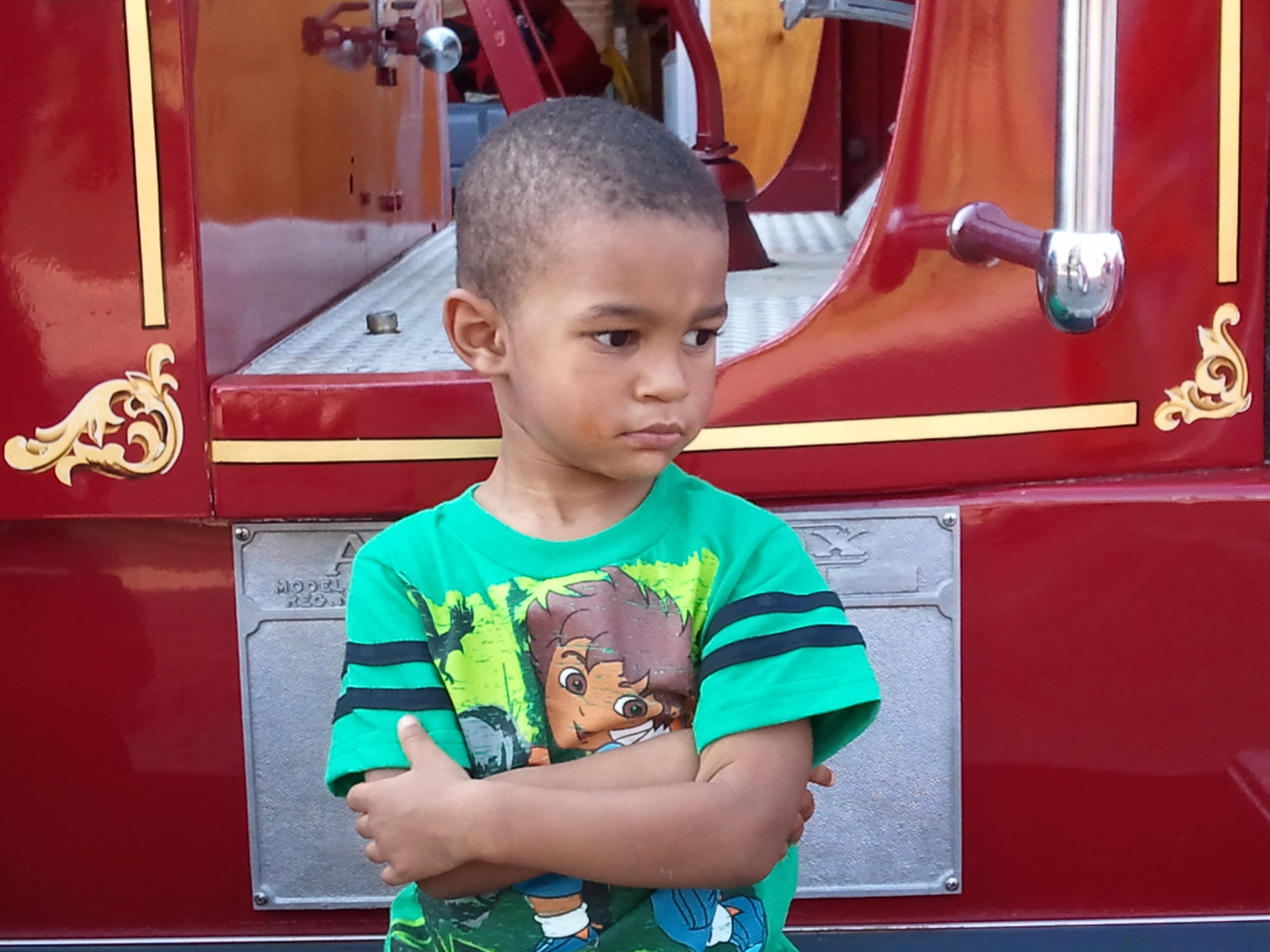 Little boy reluctantly poses on antique fire truck