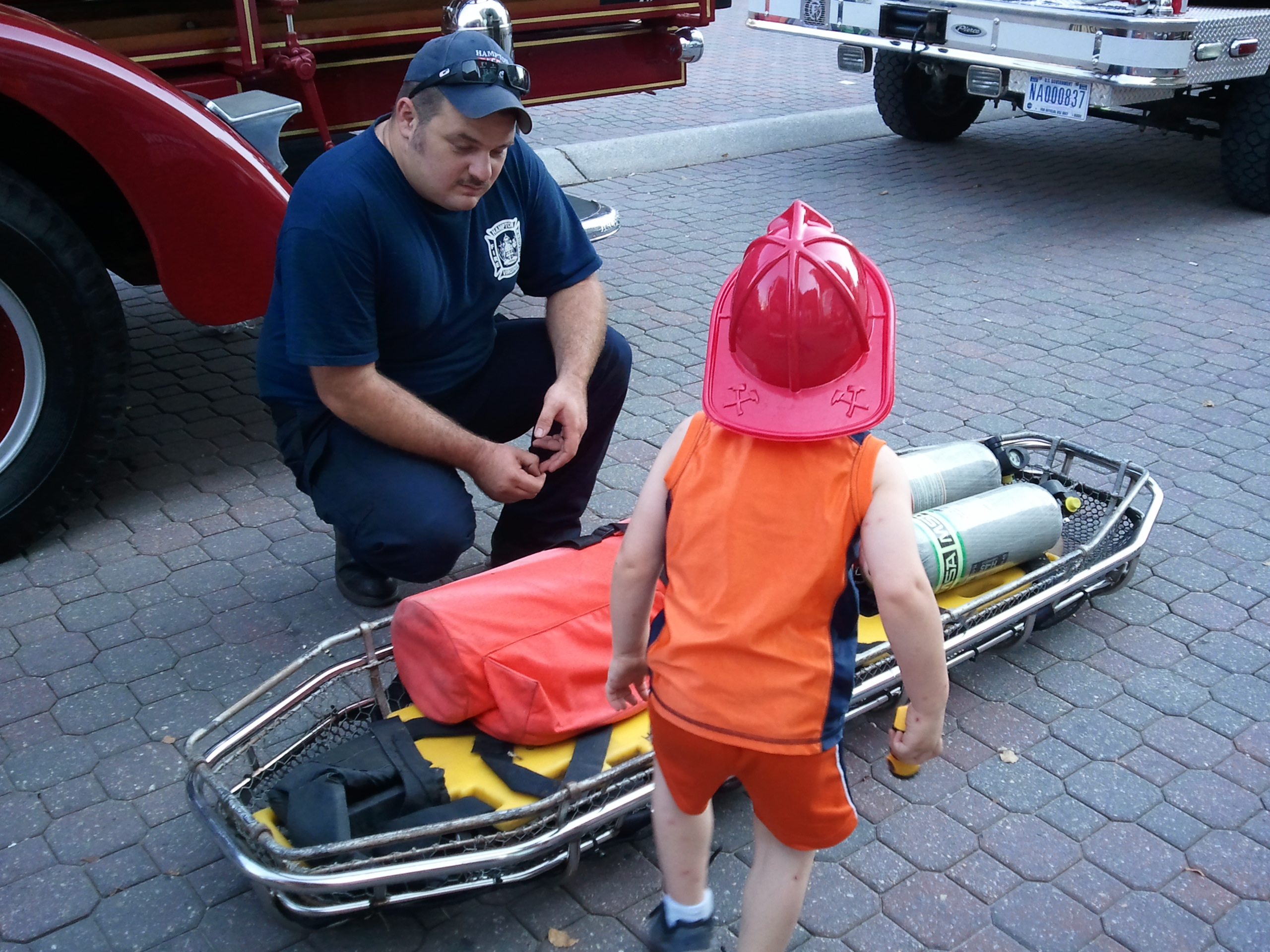 Firefighter displays equipment to child